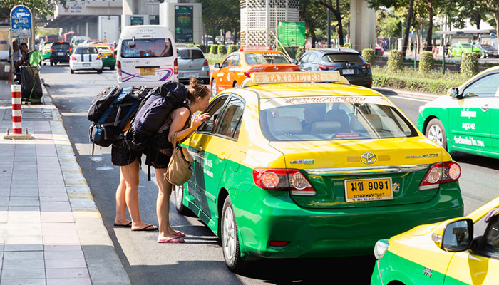 Mochileros hablando con un taxista en Bangkok